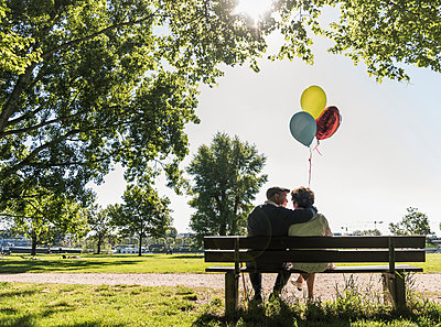 Happy senior couple with balloons sitting on bench in a park - p300m1459886 by Uwe Umstätter