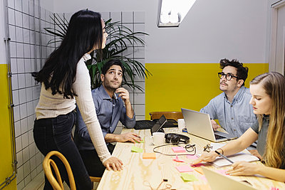 Four people discussing at desk in creative office - p426m1407170 by Maskot