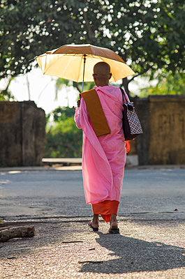 Buddhist nun walking under an umbrella in Rangoon, Myanmar, Asia. She wears a pink robe - p934m893120 by Yan Lerval photography