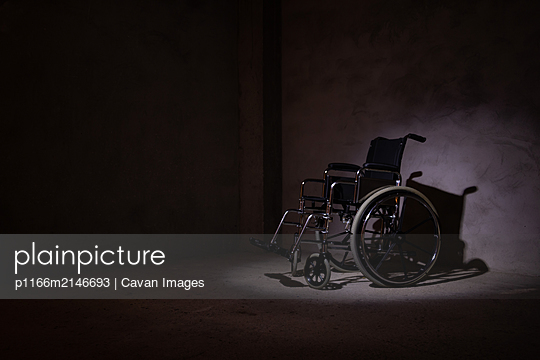 An isolated wheelchair illuminated with a light in the dark. - p1166m2146693 by Cavan Images
