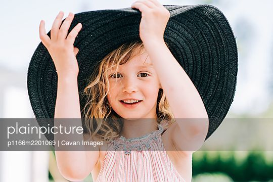 candid portrait of a young girl laughing playing with a large sun hat - p1166m2201069 by Cavan Images