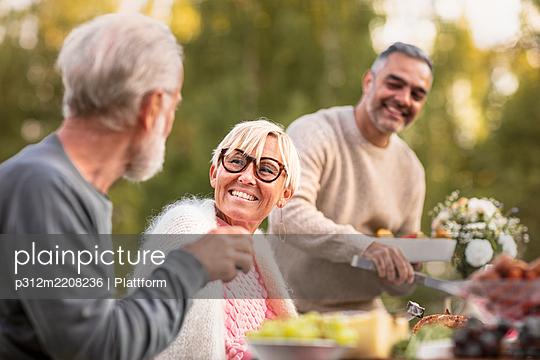 Happy woman sitting at table - p312m2208236 by Plattform