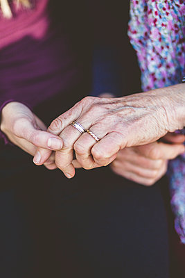 Cropped image of grandmother and granddaughter holding hands - p426m2018544 by Maskot