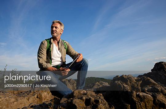 Man with digital tablet sitting on rock - p300m2290517 by Jo Kirchherr