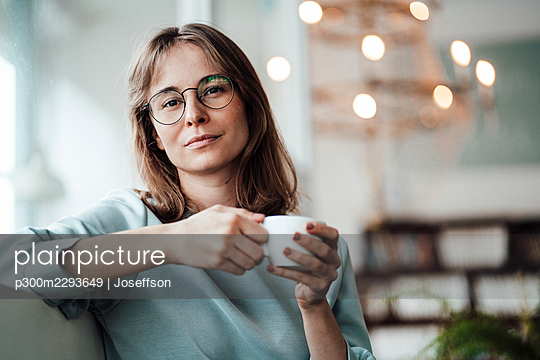 Young woman wearing eyeglasses holding coffee cup while sitting in cafe - p300m2293649 by Joseffson