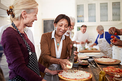 Senior women friends grating cheese over pizza in cooking class - p1023m1583958 by Trevor Adeline