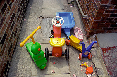 Children's ride on toys in back yard of house - p1072m829339 by Neville Mountford-Hoare
