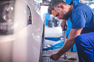 Car mechanic in a workshop changing tyre - p300m1205554 by zerocreatives