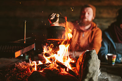 Man putting kettle on campfire - p312m2190358 by Matilda Holmqvist