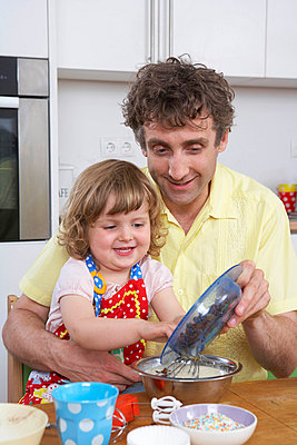 Father and daughter, preparing dessert - p4293864f by Judith Haeusler
