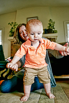 Caucasian mother helping baby walk on living room floor - p555m1420446 by Peathegee Inc