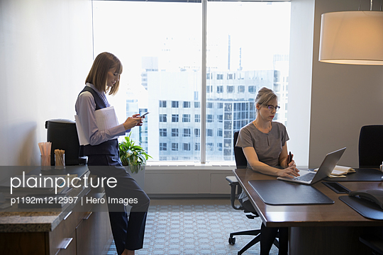 Female lawyers working at laptop and using cell phone in conference room