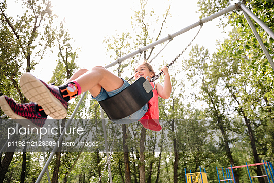 Candid portrait of young girl on swing in summer - p1192m2129889 by Hero Images