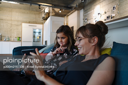 Woman and girl sitting on couch in office using smartphone - p300m2167336 von Kniel Synnatzschke