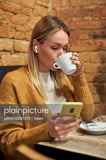 Young woman drinking coffee while using mobile phone in cafeteria - p300m2257373 by Veam