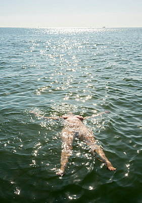 woman swimming Waddensea - p1132m1486817 by Mischa Keijser