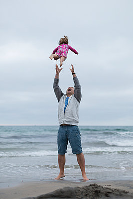Playful father throwing daughter in air while standing on shore against sky at beach - p1166m1508244 by Cavan Images