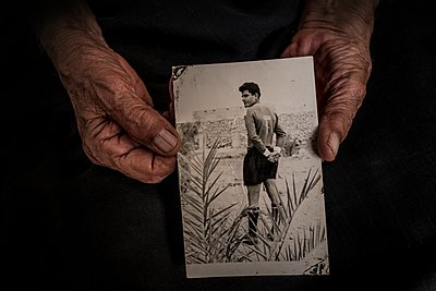 Faltige Hände halten ein altes Foto - p1508m2168821 von Mona Alikhah