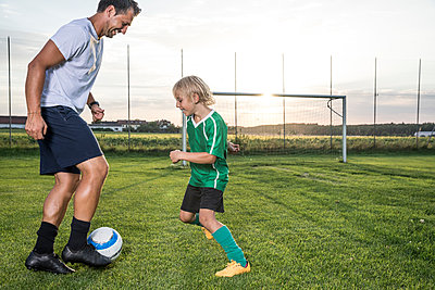Coach and young football player on football ground at sunset - p300m1580945 von Fotoagentur WESTEND61
