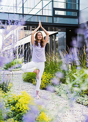 Woman practicing yoga in garden outsde office building - p300m2023824 by Uwe Umstätter