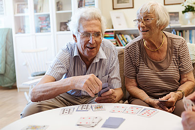 Senior couple playing cards at table in nursing home - p426m2072549 by Kentaroo Tryman