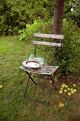 Schmutziges Geschirr auf Gartenstuhl - p432m1590632 von mia takahara