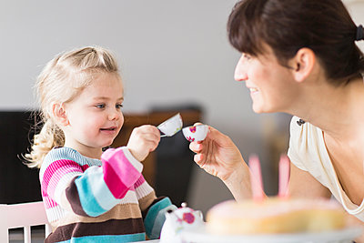 Mother and daughter playing with doll's china set - p300m2189102 by Floco Images