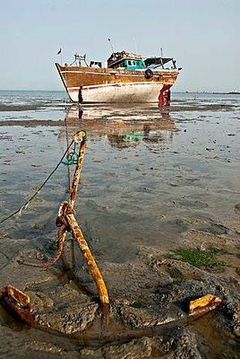 Fishing boat anchored on the sand waiting for the high tide, Bandar- Abbas, Iran - p3437929 by Guillem Lopez