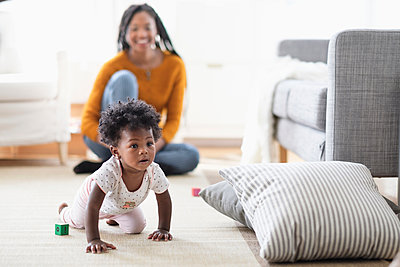 Black woman watching baby daughter crawl toward pillow - p555m1305419 by JGI/Tom Grill