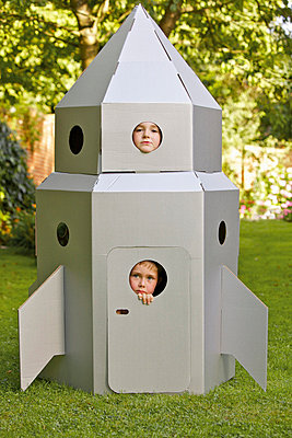 Two Boys Looking Out from Window of Cardboard Rocket Spacecraft - p669m713928 by Jutta Klee photography