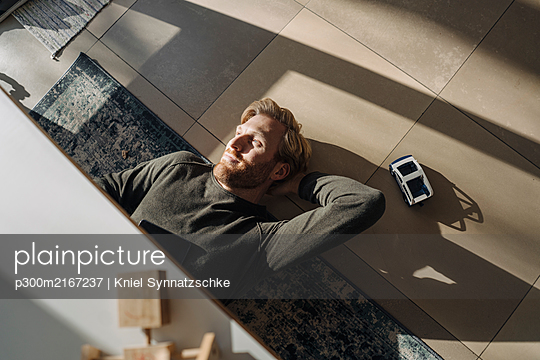Relaxed man lying on the floor at home - p300m2167237 von Kniel Synnatzschke