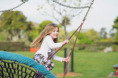 Young girl playing on a swing at a playground - p1166m2201892 by Cavan Images