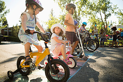 Kids on bicycles ready for race at starting line at summer neighborhood block party - p1192m2017135 by Hero Images