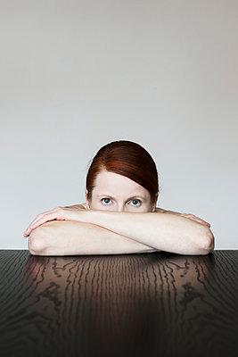 Frau am Tisch sitzend mit verschränkten Armen  - p1574m2183657 von manuela deigert