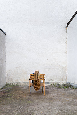 Young woman on a chair in a back yard - p1625m2210796 by Dr. med.