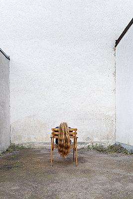 Junge Frau auf einem Stuhl in einem Hinterhof - p1625m2210796 von Dr. med.