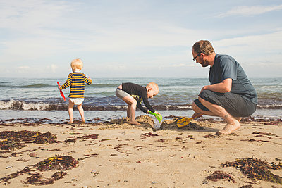 Father with two kids playing on the beach - p300m2103296 by Irina Heß