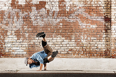 A young man doing a breakdance move balancing on his hands on the street of a city.  - p1100m1107164 by Mint Images