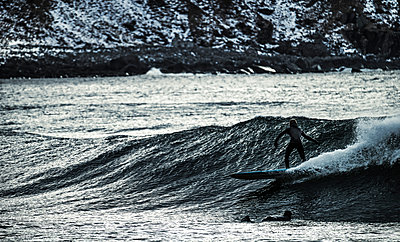 A young man surfing on an ocean with a mountain behind. - p1100m1482237 by Mint Images