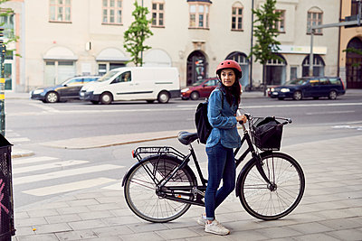 Mid adult woman standing with bicycle on sidewalk in city - p426m1506202 by Maskot