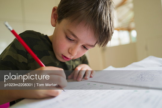 Close up focused boy home schooling - p1023m2208301 by Tom Merton