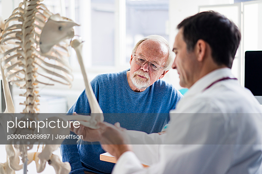 Doctor explaining bones at anatomical model to patient in medical practice - p300m2069997 by Joseffson
