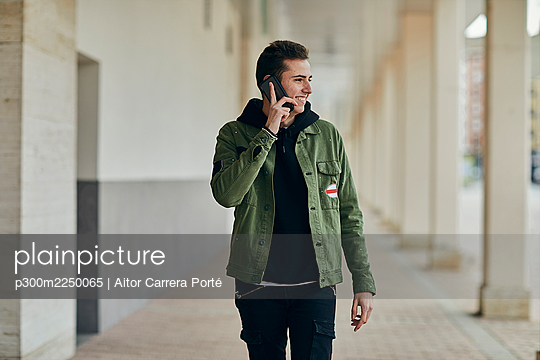 Smiling young man talking on mobile phone while looking away at arcade - p300m2250065 by Aitor Carrera Porté