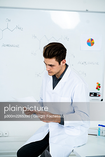 Young male scientist looking at chart while sitting on desk in laboratory - p300m2265390 by Giorgio Fochesato