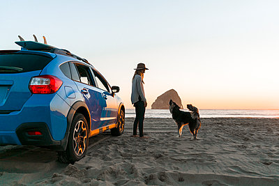 Happy woman with dog standing by car at beach - p1166m1210556 by Cavan Images