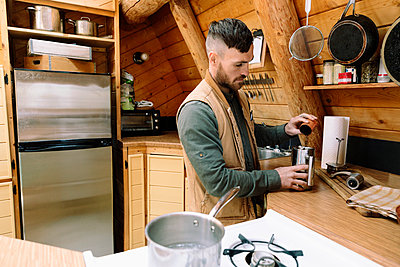 Man preparing coffee in cabin kitchen - p1192m2093889 by Hero Images