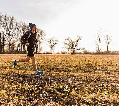 Man running in rural landscape - p300m1355867 by Uwe Umstätter