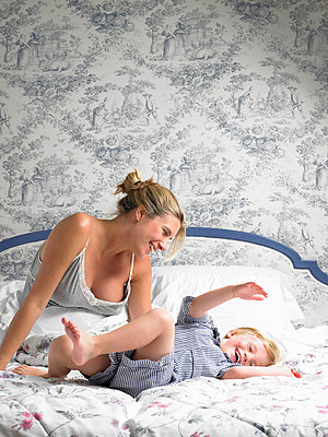 Boy jumping on his mother's bed - p4293833f by Ghislain & Marie David de Lossy