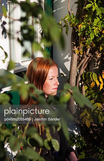 Frau sitzt vor Haustür und genießt die Sonne - p045m2055480 von Jasmin Sander