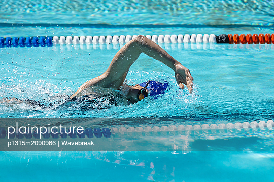 Female swimmer swimming freestyle in swimming pool - p1315m2090986 by Wavebreak
